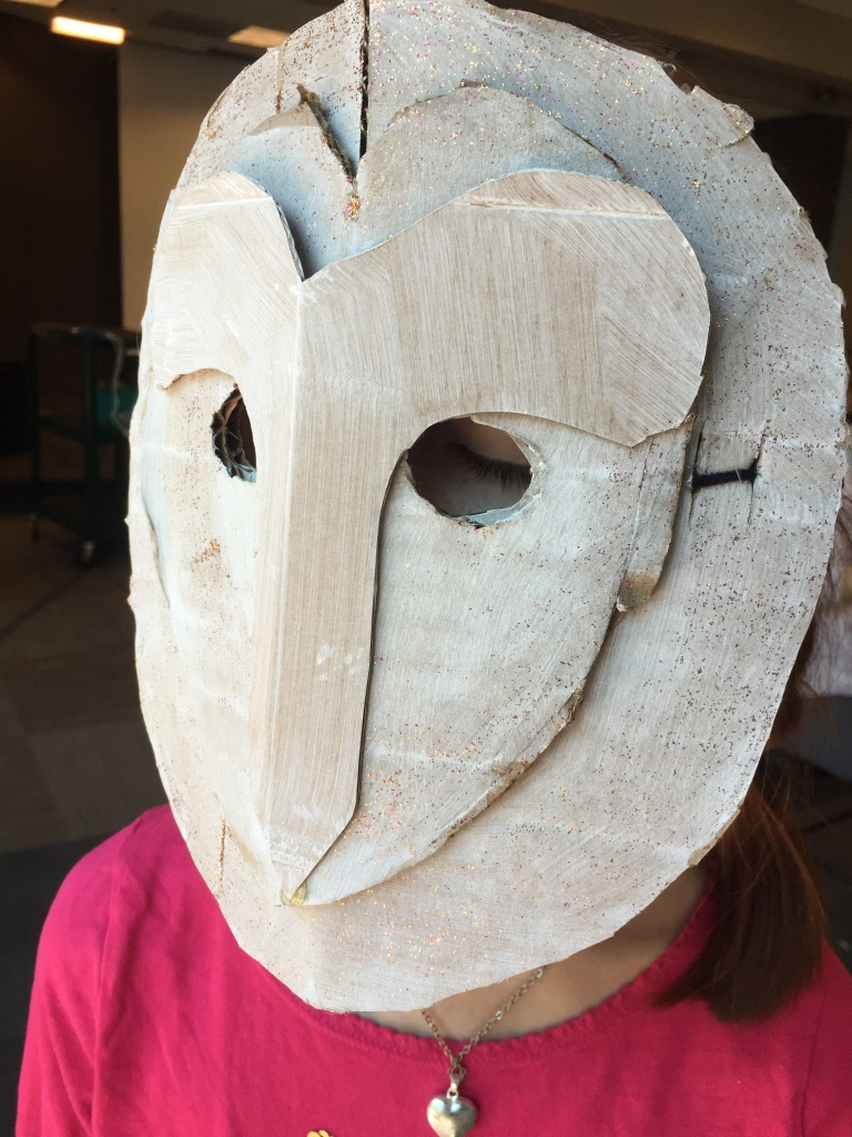 Kid wearing an owl mask